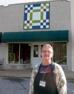 Rhonda Standifer, manager for the Thermal Belt Habitat for Humanity store in Landrum, stands in front of the newly-installed quilt block entitled Building Blocks.  This is now the eighth block on the Foothills Quilt Trail in Landrum. Also hung on April 24 were blocks nine and 10: the Liberated Log Cabin block at Elaine's Attic  and Fergus the Fox on the Wallace Building, both located on E. Rutherford Avenue in downtown Landrum.  A grant from the Mary F. Kessler Fund at the Polk County Community Foundation provided these blocks for the developing quilt trail. (photo submitted by Ellen Henderson)