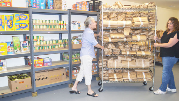 Outreach's Carol Newton and Michelle Reedy move a cart in an expanded 1,400 square foot pantry at the Columbus Facility. (photo by Samantha Hurst)