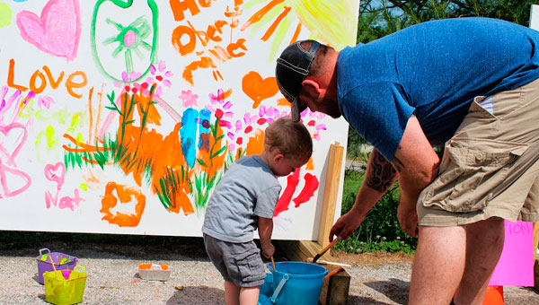A little boy and his dad create art on the makeshift mural set up during Sauda's Streets Alive event Saturday, June 8.