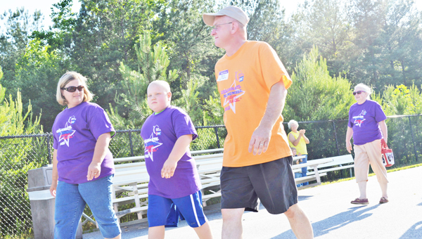 Julie Wilson (left) and David Moore (right) walk with Bryson Owen (middle) as he leads the cancer survivor walk at Relay for Life, held at the Polk County Middle School on Friday, May 31. See more photos of the event at www.tryondailybulletin.com (photo by Leah Justice)
