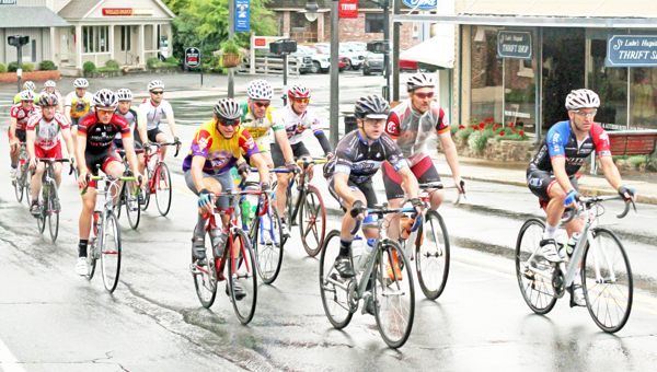 Participants in the 30th annual Fabulous Fourth Bike Tour ride through downtown Tryon despite early morning showers on July 4. (photo by Lorin Browning)