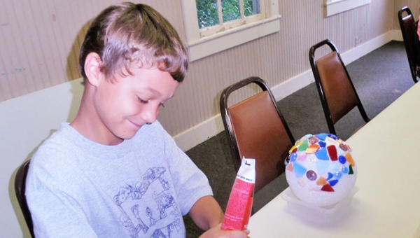 This summer 4-H'ers learned a new craft. They created garden spheres to beautify their yards. In the photo Ellis Parsons is gluing his glass to a Styrofoam ball and once the glue dries he will apply mortar. (photo submitted by Helen Clark)