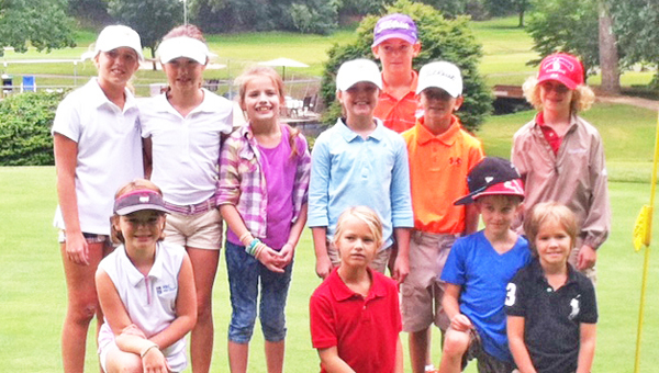 Eleven junior golfers played in the annual Tryon Country Club Parent/Child Golf Tournament held Saturday, Aug. 17. Shown are golfers (kneeling) Ellie Mitchell, Hayden Blackwell, Carson Metcalf and Lawson Carter; (standing) Rollins Carter, Sydney Metcalf, Verae Upton, Ella Waldman, Grayson Jones and Cole Pereira. Also pictured (middle photo) are overall champions Evan Jones, playing with his grandfather Hub Arledge; and (right photo) girl's division winner Ellie Mitchell, playing with her father, Mike Mitchell. (photos submitted by Renea Waldman)