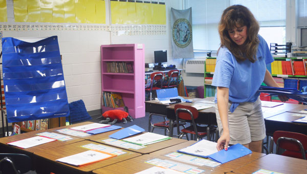 Michelle Richardson is returning for her first year back in the classroom after taking several years off to raise her daughters. Richardson is seen here passing out folders to each desk in her second-grade classroom at Polk Central. (photo by Samantha Hurst)
