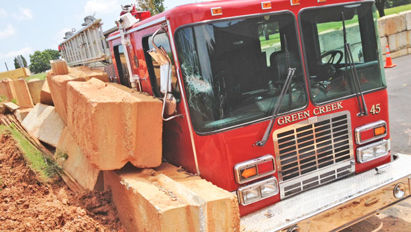 Thick blocks that made up a retaining wall at the Green Creek Fire Department are seen here smashed against one of the department's fire engines with crumbling red clay falling in behind them. Another round of thunderstorms that moved through the area over the weekend brought several inches of rain each day. Friday, Aug. 9 Tryon's water plant recorded 1.68 inches of rain. On Saturday, Aug. 10 the plant saw 1.15 inches of rain and on Sunday, Aug. 11 the area got 1.12 inches of rain. See the full story on page 3.