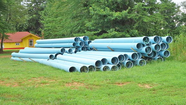Pipes sit along the side of Hwy. 9 waiting to be placed in the ground as part of the new waterline. (photo submitted)