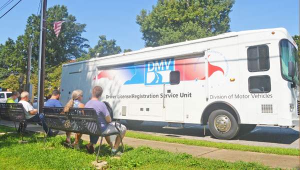 Polk County residents sit on benches outside the mobile DMV unit Thursday, Aug. 22. Polk County commissioner Keith Holbert said he received word recently that the county has been approved for a permanent office. See full story on page 6. (photo by Samantha Hurst)