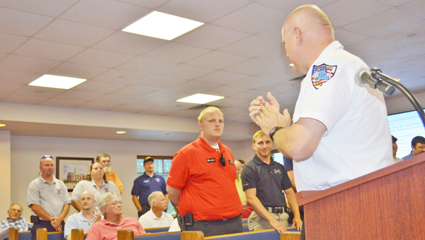 Polk County EMS Director Michael Crater, at right, recognized emergency personnel and department of transportation and utility workers for their response to heavy rains in July that caused several county roads to wash out. Crater recognized the individuals during the Polk County Board of Commissioner meeting held Monday, Aug. 5. (photo by Leah Justice)
