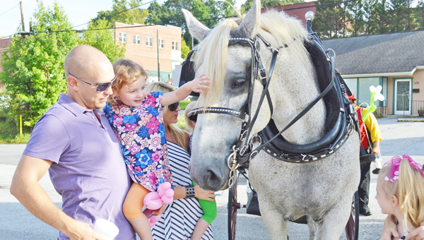 Carolina Horse and Carriage, out of Landrum, gave visitors to the Tryon gallery Trot tours through downtown Tryon on Saturday, Aug. 10. Pictured is Tim Ballew with his daughter, Lilly, petting Sampson the horse. At left also is Jennifer Ballew. At right is Sydney Walraven. (photo by Leah Justice)