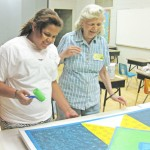 Zoe McDowell and an area quilter work on one of two squares to be displayed on campus.