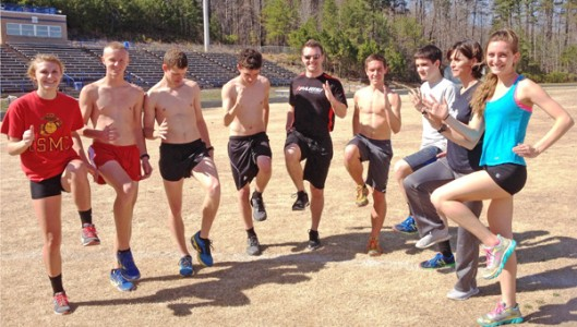 Colby Harris, Director of Parisi Speed School at Xcel Sportsplex in Hendersonville (center), demonstrates proper running technique for Polk High Track Team Members at Wolverine Stadium, (left to right) Shea Wheeler, Mitchell Brown, Jacob Collins, Isaias Akers, Colby Harris (Instructor), Eli Hall, Jacob Wolfe, Coach Jenny Wolfe, Emma Wagoner. (photo submitted by Jenny Wolfe).