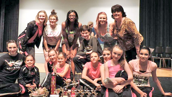 Dance Dynamics competition dancers and instructors show off their winnings with big smiles and trophies. (photo submitted by Missy Fincher)
